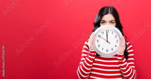 Fotografie, Obraz  Young woman holding a clock showing nearly 12