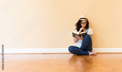 Fotomural  Young woman reading a book in a big room