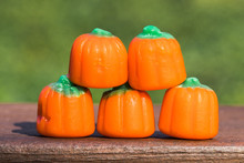 Horizontal Closeup Photo Of Candy Pumpkins In A Pyramid Shape On Wood