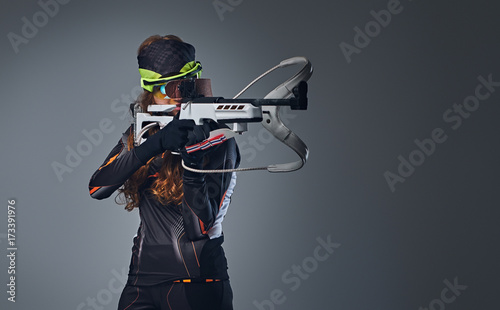 Photo Redhead female Biathlon champion aiming with a competitive gun.