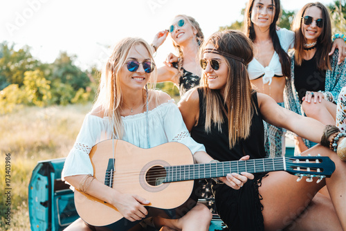 Poster Magasin de musique Girls are sitting on the trunk with a guitar