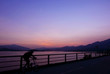 Silhouette of bicycle, fence, mountain, gradient purple sky