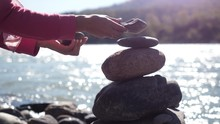 Female Hands Putting Pebble Stack Next To The Mountain River On Sunny Day With Lens Flare Effects
