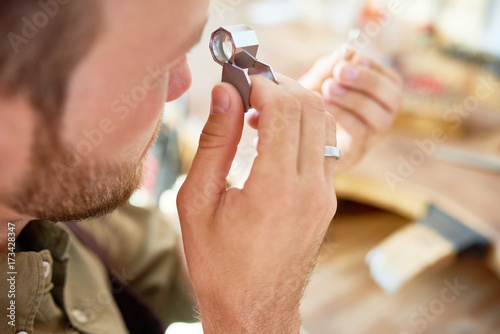 Fotografie, Obraz  Closeup portrait of jeweler inspecting ring through magnifying glass in workshop