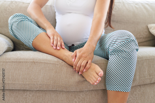 Pregnant hands massaging swollen foot Wallpaper Mural