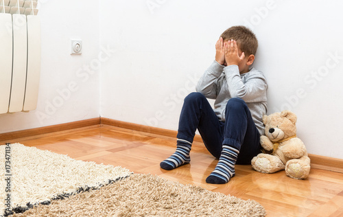 Sad boy is sitting on the floor with his hands on his face
