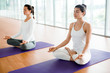 Two young women practicing zen exercises on mats in gym