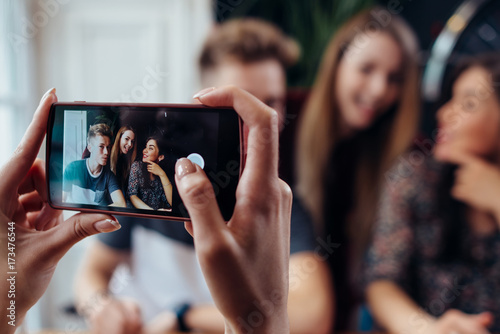 Obraz Female hands taking photo with smartphone of young cheerful friends, blurred background - fototapety do salonu