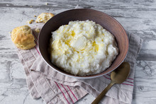 Southern Grits With Bisquit And Butter In Rustic Setting Closeup