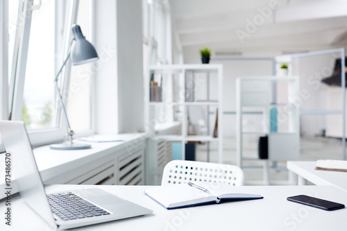 Fotografia  Modern workplace with laptop and notepad, interior of spacious open plan office