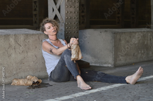 Láminas  a punk woman under a bridge with bottles of alcohol nearby and a bottle in a bro