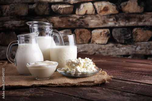 Poster Produit laitier milk products. tasty healthy dairy products on a table on. sour cream in a bowl, cottage cheese bowl, cream in a a bank and milk jar, glass bottle and in a glass