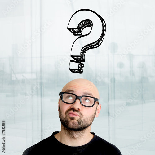 Valokuva  Portrait of an attractive stressed geek man with question mark icons surrounding