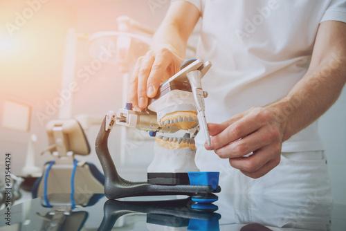 Fotografia  Dental technician working with articulator in dental lab