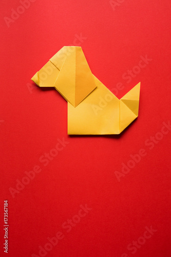 yellow folded origami dog on red paper background vertical new year postcard poster