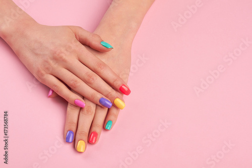 Female hands with stylish colorful nails. Beautiful woman hands with pastel colors nails on pink background, copy space.