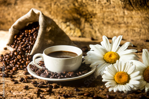 Wall Murals Cafe Coffee cup and fried coffee beans on a wooden table with beautiful white flowers on a wood background