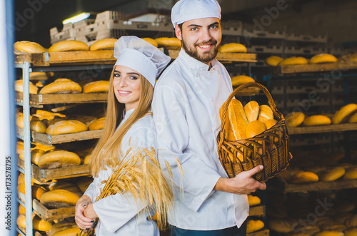 In de dag Bakkerij Bakery. Bread. Two bakers. Young beautiful workers of a bakery on a background of racks with bread. Industrial production of bakery products. Couple. Workers. Boy and girl