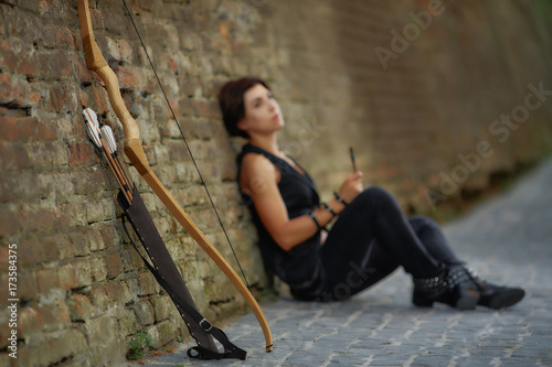 Fototapety, obrazy: Distance view of woman resting after shooting from bow.