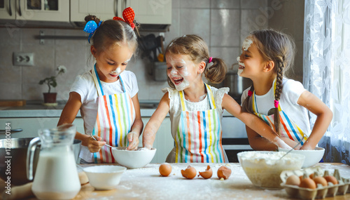Cuadros en Lienzo happy sisters children girls bake cookies, knead dough, play with flour and laug