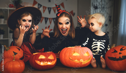 Deurstickers Franse bulldog family mother and children in costumes and makeup to halloween with pumpkin in dark .