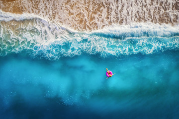 Plakat Aerial view of slim woman swimming on the pink swim ring in the transparent turquoise sea in Oludeniz,Turkey. Summer seascape with girl, beautiful waves, colorful water at sunset. Top view from drone