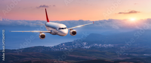Türaufkleber Flugzeug Passenger airplane. Landscape with white airplane is flying in the orange sky with clouds over mountains, sea at colorful sunset. Passenger aircraft is landing. Commercial plane. Private jet. Travel