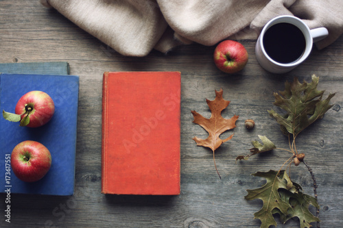 Fotografija  Autumn season still life with red apples, books, blanket, black coffee mug and fall leaves over rustic wooden background