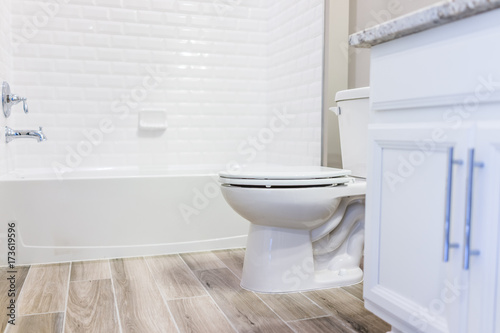 Fotografía  Modern white plain clean toilet bathroom, bathtub with shower tiles and hardwood