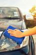 Girl's hand wiping on car's headlight.