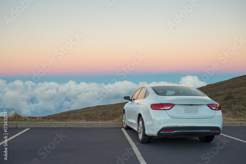 White car in mountains above the clouds at sunset or sunrise Fototapeta