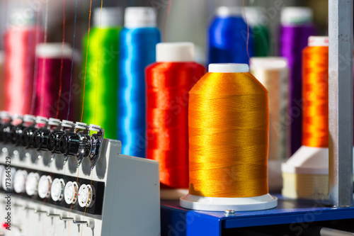 Photo Spools of color threads closeup, spinning machine
