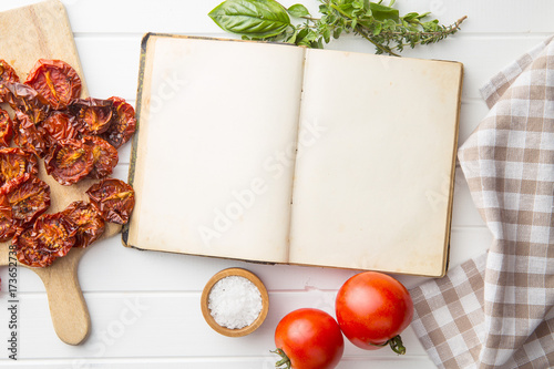Fototapeta Old recipe book with tomatoes, herbs and salt. obraz