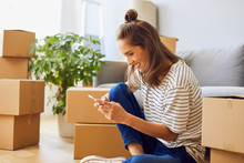 Beautiful Young Woman Texting While Moving To New Apartment