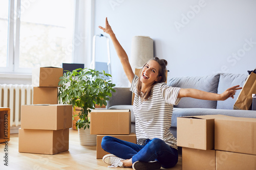 Fotografiet  Young woman sitting in new apartment and raising arms in joy after moving in