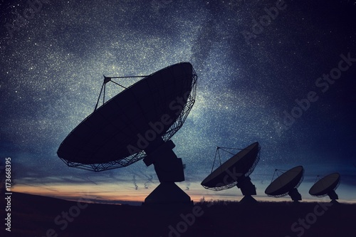 Fotografía  Silhouettes of satellite dishes or radio antennas against night sky