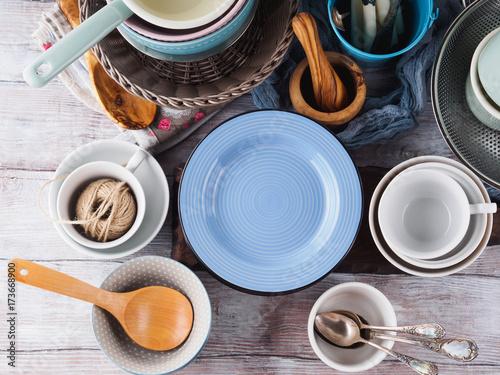 Zdjęcie XXL Ceramiczna i emaliowa crockery tableware na drewnianym tle. Pastelowe kolory vintage. Niebieski pusty talerz na tekst