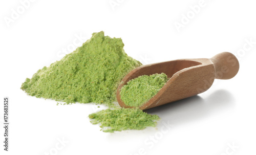 Wheat grass powder and wooden scoop on white background