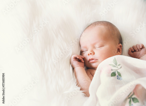 Obraz Sleeping newborn baby in a wrap on white blanket. - fototapety do salonu