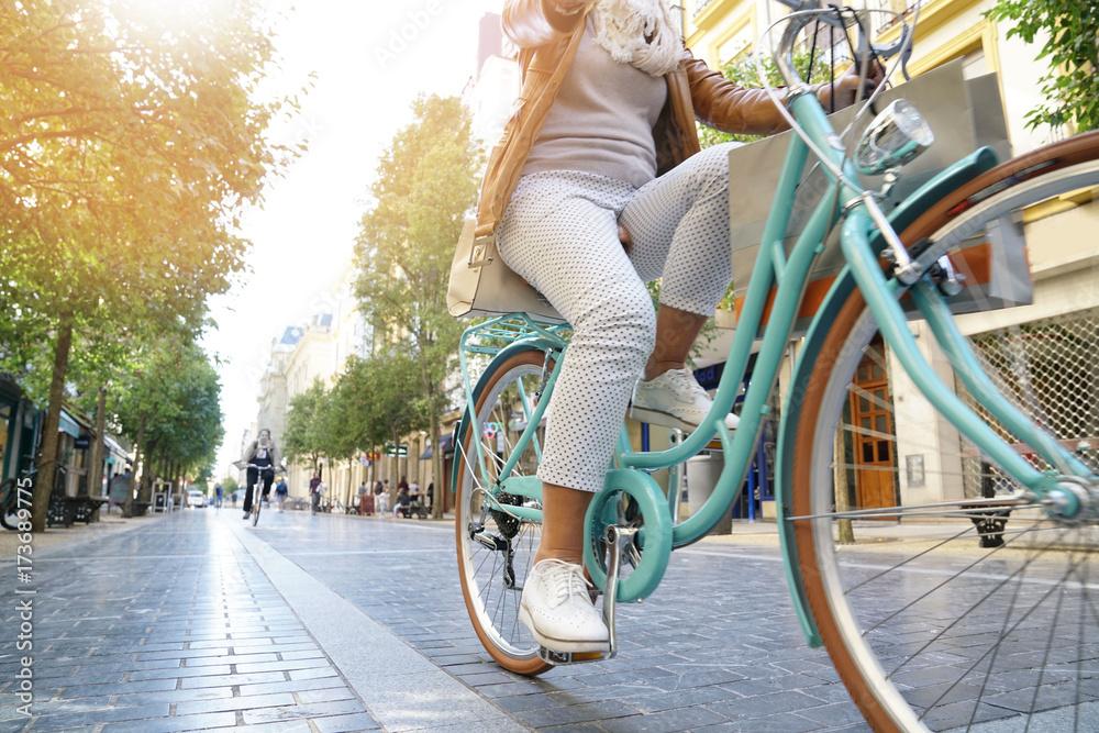 Fototapeta Senior woman riding city bike in town