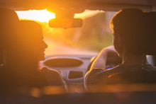 The Couple Drive A Car On The Background Of The Sunset