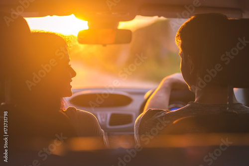 Cuadros en Lienzo The couple drive a car on the background of the sunset