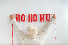 Woman Attaching Christmas Bunting On Wall