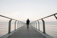 Back View Of Man Walking On Bridge Over Sea