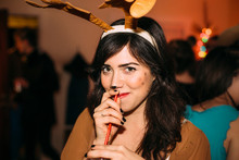 Young Smiling Brunette Woman Dressed As Reindeer Holding Straw And Drink At Christmas Party