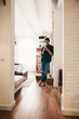 Latin man standing using phone at home.