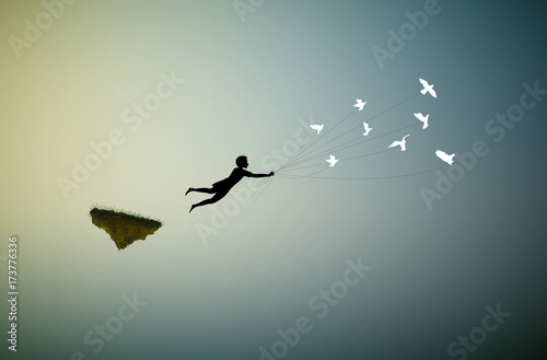 Fotografia  boy is flying away and holding pigeons, fly in the dream land,fly away, shadows,
