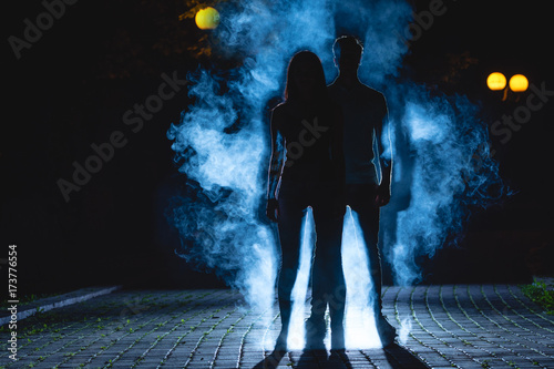 Fotografía The man and woman stand on a dark alley on the blue fume background