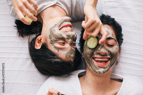 Overhead view of happy friends with beauty mask