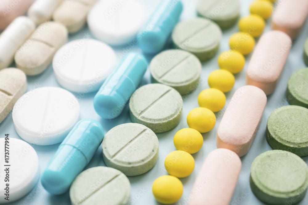 Fototapeta Opioid painkillers crisis and drug abuse concept. Opioid and prescription medication addiction epidemic. Different kinds of multicolored pills. Pharmaceutical medicament background